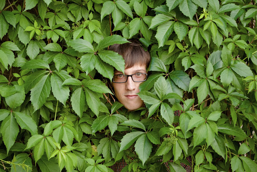 man hiding in bushes, peeking out